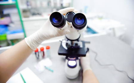 medical technical equipment: Close-up photo of scientist hands with microscope, examining samples and liquid. Medical research with technical equipment.