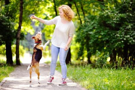 persona saltando: Mujer hermosa joven que juega con el perro beagle en el parque de verano