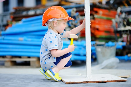 Portrait of little builder in hardhats with hammer working outdoors