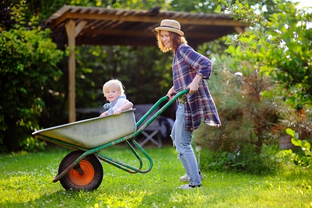 domestic garden: Adorable toddler boy having fun in a wheelbarrow pushing by mum in domestic garden, on warm sunny day. Active outdoors games for kids in summer. Stock Photo