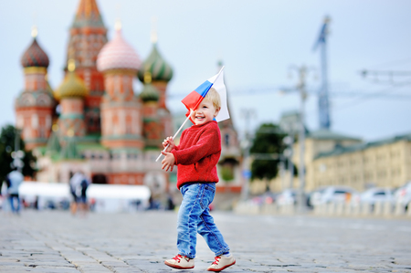 red square: Cute toddler boy running with russian flag with Red Square and Vasilevsky descent on background Stock Photo
