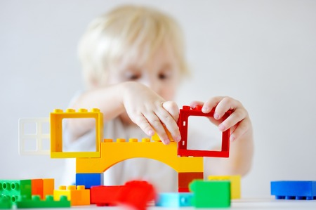 Cute toddler boy playing with colorful plastic blocks indoors, focus on hands Stock Photo