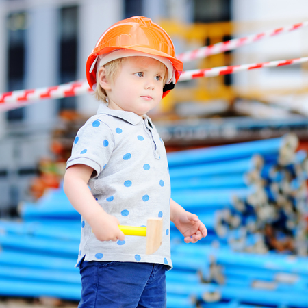 Portrait of serious little builder in hardhats with hammer working outdoors