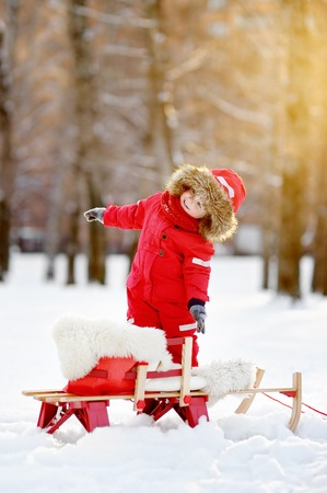 to steer a sledge: Portrait of beautiful toddler boy having fun in winter park. Toddler playing with fresh snow Stock Photo