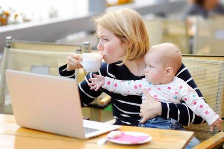 madre soltera: joven madre cansada que trabaja oh su portátil, sosteniendo la hija y el consumo de café Foto de archivo