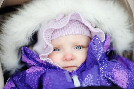 Winter portrait of baby girl in stroller outdoors