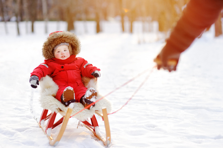 to steer a sledge: Father and his toddler son having fun in winter park. Games with fresh snow
