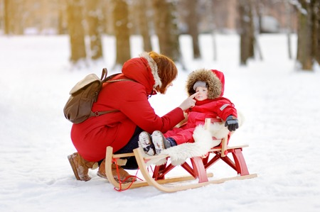 to steer a sledge: Portrait of beautiful toddler boy and his mother having fun in winter park. Family game with fresh snow