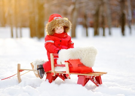 to steer a sledge: Portrait of beautiful toddler boy having fun in winter park. Game with fresh snow