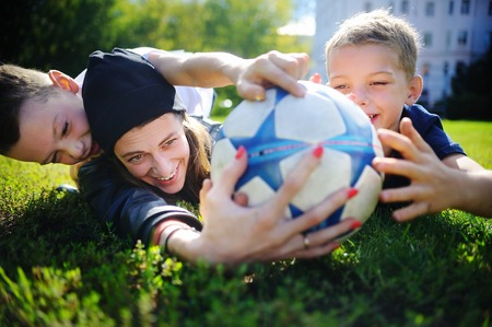 boys playing: Young mother and her little boys playing a soccer game on sunny summer day. Family having fun with ball outdoors
