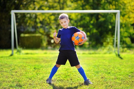 football play: Little boy having fun playing a soccer game on sunny summer day