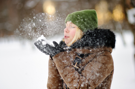 having fun in the snow: Outdoors portrait of young beautiful woman having fun in winter. Active game with snow
