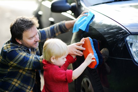 Middle age father with his toddler son washing car together outdoors