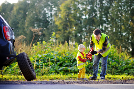 Family of two: father and his little son repairing car and changing wheel together on summer day