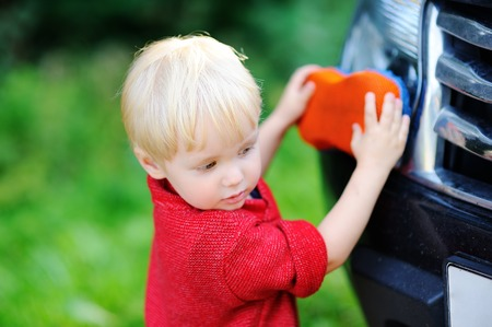 Cute toddler son playing washing fatherss car outdoors