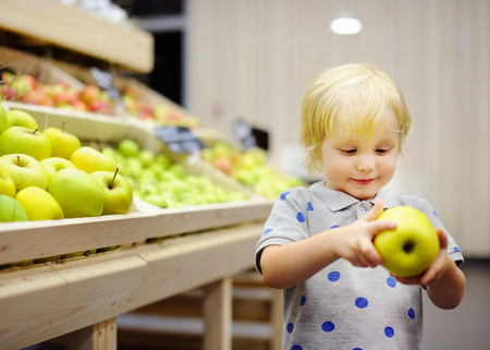 produce departments: Cute toddler boy in a food store or a supermarket choosing fresh apples. Healthy lifestyle for young family with kids