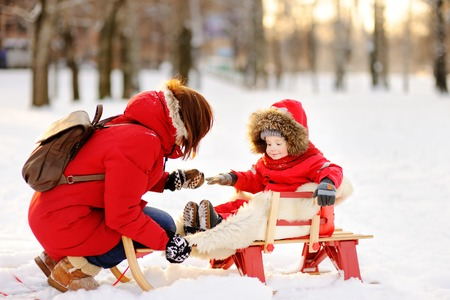 to steer a sledge: Portrait of beautiful toddler boy and his mother having fun in snowy park. Active winter game