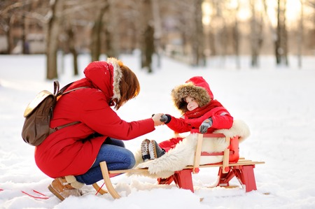 to steer a sledge: Portrait of beautiful toddler boy and his mother having fun in winter park