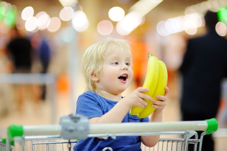 Cute toddler boy sitting in the shopping cart and holding bananas in a food store or a supermarket. Family shopping