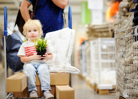 home furnishings: Family with little boy choosing the right furniture for their apartment in a modern home furnishings store. New home for family with kids Stock Photo