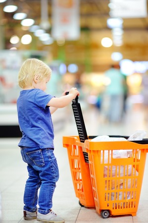 produce departments: Toddler boy with shopping cart in a food store or a supermarket. Family shopping