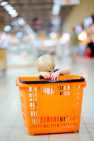 Toddler boy with shopping cart in a food store or a supermarket. Family shopping. Focus on child hands