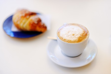 Tasty breakfast in a Italian street cafe - cup of coffee and croissant on white table
