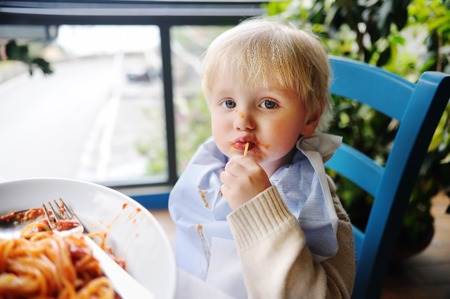 smeared baby: Cute toddler boy eating pasta in Italian indoors restaurant. Healthyunhealthy food for little kids