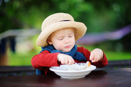 Cute toddler boy eating rice cereal outdoors. Healthy food for little kids Stock Photo