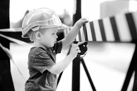 Portrait of cute little builder in hardhats with ruler working outdoors. Childhood concept