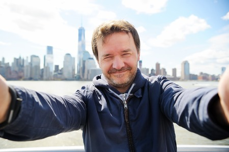 middle age man: Middle age man making a self portrait (selfie) with Manhattan skyscrapers in New York City