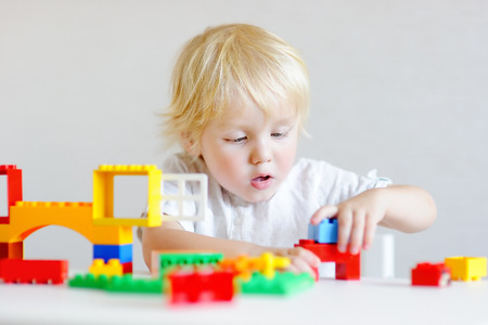 Cute little boy playing with colorful plastic blocks indoors
