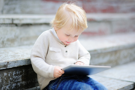 Cute blonde toddler boy playing with a digital tablet outdoors 版權商用圖片