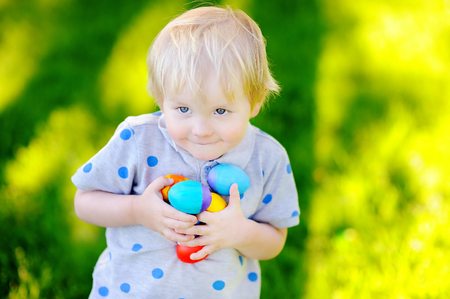 Little boy hunting for easter egg in spring garden on Easter day. Cute little child celebrating feast Stock Photo
