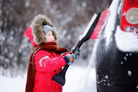 Cute little child helping to brush a snow from a car. Toddler boy using tool for cleaning fathers car