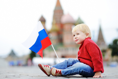 Cute toddler boy sitting and playing with russian flag with Red Square and Vasilevsky descent on background