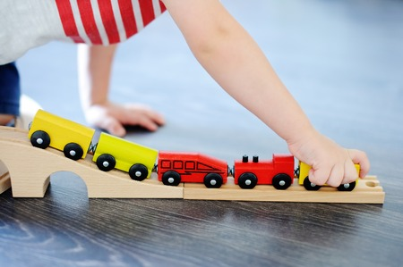 Close up photo of toddler boy playing with toy wooden train at home. Game for little children
