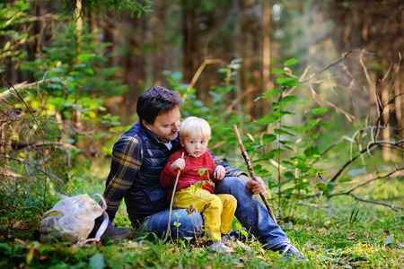 Father and his little son walking during the hiking activities in forest at sunset. Family leisure time Stock Photo