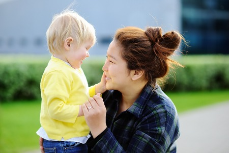 solicitous: Young loving asian women with cute caucasian toddler boy. Babysitting concept