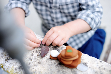 Little boy playing with little stones outdoors. Toddler child builds tower Stock Photo