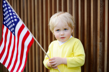 Cute toddler boy holding american flag. Independence Day concept. Stock Photo