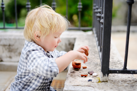Cute blonde little boy playing with little stones outdoors. Toddler child builds tower