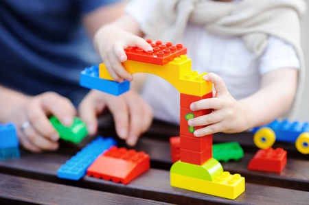 Father with his toddler son playing with colorful plastic blocks. Family leisure with little kids