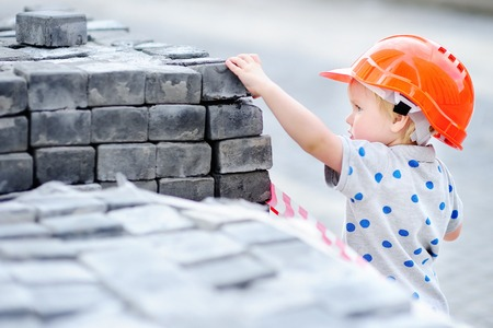 Portrait of little builder in hardhats with hammer working outdoors. Childhood concept