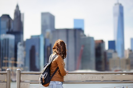 Young female tourist enjoy panoramic view with Manhattan skyscrapers in New York, USA. Most famous skyscrapers in world