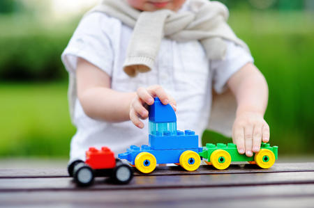 Toddler boy playing with toy train outdoors at warm summer day. Toys for little children Stock Photo