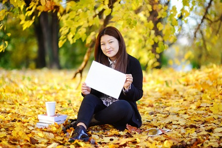 Beautiful asian girl outdoors portrait. Young woman studyingworking and enjoying beautiful sunny autumn day. Student holding blank whiteboard in her hands Stock Photo