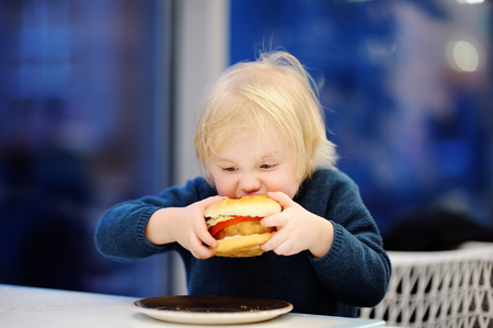 Cute blonde boy eat hamburger at fast food restaurant. Child unhealthy meal concept
