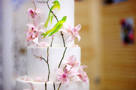 Traditional anniversarywedding multi-layer cake. Beautiful delicious sweet dessert decorated with flowers on blurred background