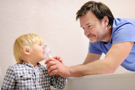 Middle age father helping his toddler son with inhalation therapy by the mask of inhaler. Image of a little kid with respiratory problem or asthma. Sick little boy with clear oxygen mask.